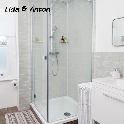 Стильная душевая кабина из стекла с поддоном в ванной отделанной плиткой в стиле метро и на полу плитка под дерево