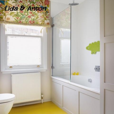 Традиционная ванная комната с  желтым полом и душевой из стекла прямо в ванне